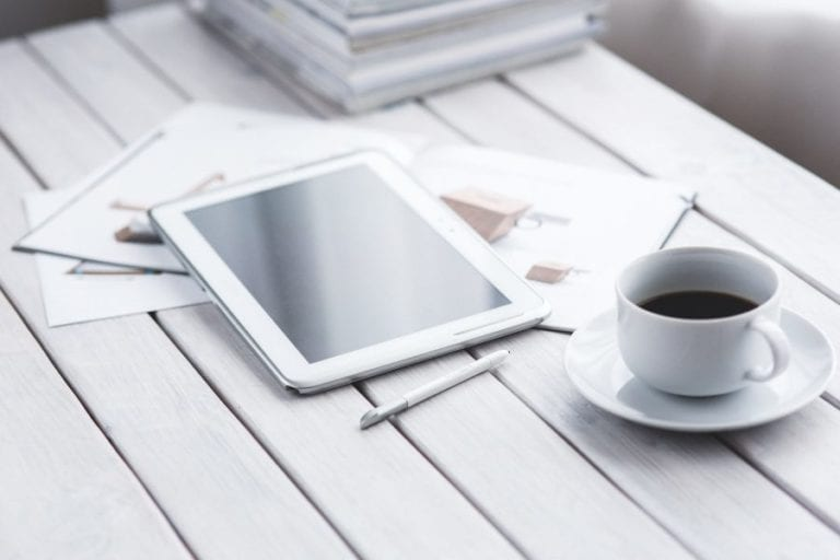 Tablet with a cup of coffee next to it